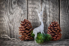 Home decor pine cones. And white deer on a wooden background Stock Image