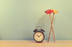 Home decor : Vintage clock and vase flowers. Clock and flower in vase on a blue wall table Stock Image