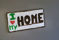 Home Decor Wooden Wall Sign I Love My Home. Wooden Wall sign saying `I love my home`. Love is symbolized as heart shape Royalty Free Stock Photos