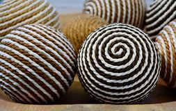 Home decor: woven decorative balls on wooden background stock photography