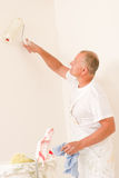 Home decorating mature man with paint roller. Home decorating mature man painting white wall with roller royalty free stock photography