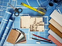 Home decorating tools standing on house bluprints. 3D illustration.  Royalty Free Stock Images