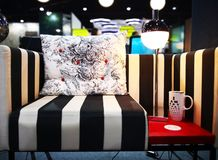Home decoration concept. White cushion with black flowers patter. N, are placed on couch with black and white stripes. The side has a lamp and a coffee mug stock photography