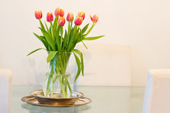 Home decoration: vase of tulips on glass table. Home interior decoration, vase of tulips on glass table Royalty Free Stock Image
