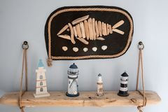 Free Home Decoration With Souvenirs From Summer Holiday. Picture With Fish And A Shelf With Lighthouses Stock Image - 156567161