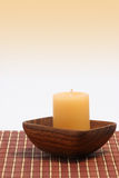 Home decorations 32. A vanilla candle in an exotic holder made of wood Stock Images