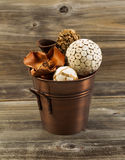 Home Decorations inside of Metal Bucket on Aged Wood Royalty Free Stock Photography