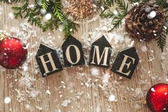 Home decorations in the wooden background of a letter with an inscription home. Christmas decorations and snow. House, comfort