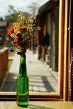 Home decorative flower bunch in green bottle on window light, copy space stock image