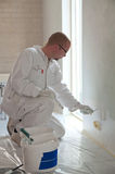 Home decorator painting a wall. Kneeling home decorator painting a wall white with a roller stock images
