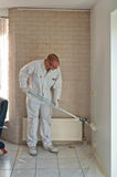 Home decorator painting a wall with a roller. Home decorator painting a wall white with a long roller Stock Photo