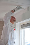 Home decorator painting a wall. White with a roller Stock Photo