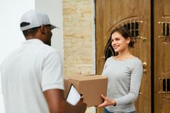 Home Delivery. Courier Delivering Package To Client. Smiling Woman Receiving Box From Delivery Man Near Door. High Resolution royalty free stock photos