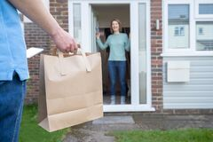 Free Home Delivery Of Takeaway Food Outside House Observing Safe Social Distancing During Coronavirus Covid-19 Pandemic Stock Images - 179133654