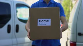 Home delivery service courier in uniform holding cardboard box, express shipping. Stock footage stock video