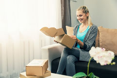 Home delivery - smiling young woman opening cardboard box. Home delivery - smiling young woman sitting on couch and opening cardboard box Royalty Free Stock Images