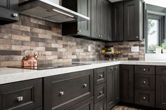 Home design remodel dark kitchen cabinets with stone back splash. Copper tea kettle royalty free stock image