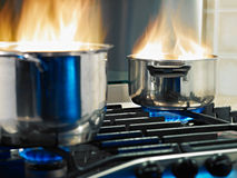 Home disasters. Pans in fire on stoves. Horizontal shape Stock Image
