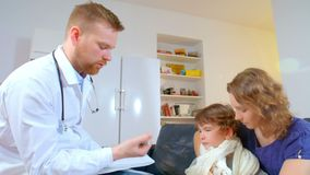 Home doctor came to sick boy and his mother. he examines a child and records readings in notebook stock footage