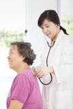 Home doctor measuring senior woman blood pressure Royalty Free Stock Photos
