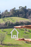 Home drawing in the hills. House dreams in hand on nature background Stock Photos