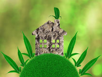 Home with ecological materials on the grass, with green leaves. Abstract environmental backgrounds. 3D render Stock Photo