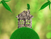 Home with ecological materials on the grass, with green leaves. Abstract environmental backgrounds. 3D render Stock Photos