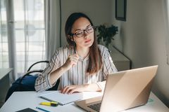 Home education or business or planning. A young beautiful student girl does homework or writes a to-do list or this girl works in a home office. Home education stock photos