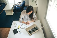 Home education or business or planning. A young beautiful student girl does homework or writes a to-do list or this girl works in a home office. Home education stock photography