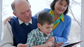 Home education, child with grandparents read book at leisure