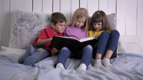 Home education, clever cute little children doing homework and reading book with happiness sitting on bed