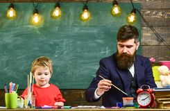 Home education concept. Father and son painting together. Developing kids creativity.  Royalty Free Stock Photography