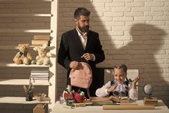 Home education and family concept. Kid and man by desk. Home education and family concept. Kid and men by desk with school supplies. Girl and father in classroom stock images