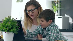 Home education, little boy with mother learn lessons using laptop. On kitchen stock video