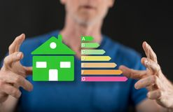 Concept of home energy efficiency. Home energy efficiency concept between hands of a man in background royalty free illustration