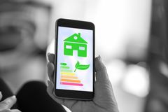 Home energy efficiency concept on a smartphone. Smartphone screen displaying a home energy efficiency concept royalty free stock photos