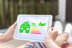 Home energy efficiency concept on a tablet. Female hands holding a tablet with home energy efficiency concept royalty free stock images
