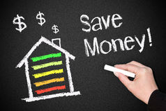 Home energy efficiency. Hands writing the words save money next to a house with dollar signs, energy efficient concept royalty free stock photography