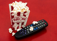 Home entertainment. A red and white container of popcorn on a wood background, Home entertainment Stock Images