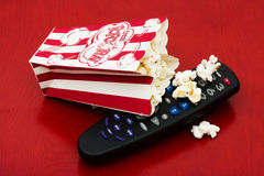 Home entertainment. A red and white container of popcorn on a wood background, Home entertainment Royalty Free Stock Photos