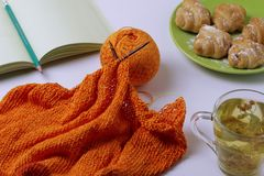 Top view of knitting from orange yarn, lime tea and delicious croissants. Home environment for relaxing. Bluer effect. Home environment for relaxing. Bluer royalty free stock photography