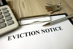 Home eviction notice legal document with pen calculator and keys