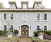 Home exterior of large grey classic house with many narrow windows. Stock Image