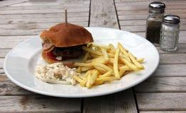 A HOME fêz o Hamburger e as microplaquetas e a salada de repolho Foto de Stock