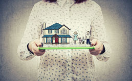 Home family insurance. Young woman holding tablet showing display with family and house hologram. Home insurance and family protection concept Stock Photo