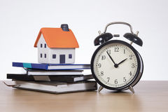 Home finance concept with ticking clock and books. A stack of bank books with a model house and ticking alarm clock on a timber desk with white copy space in a stock photo