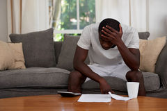 Home finance debt man. Disapointed troubled african black man sitting on sofa couch calculating home bill finance debt in living room Royalty Free Stock Images