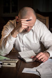Home finances. Man with checkbook and calculator concentrating over finances Royalty Free Stock Photos