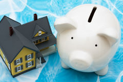 Home Finances. Model house with piggy bank on blue background. home finances Stock Photography