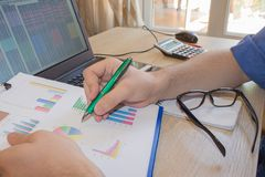 Home finances, investment, economy. person Man pointing writing goals on a paper,writing business plan at workplace, man holding p. Ens, papers, notes in stock image